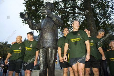 Former South African rugby player Francois Pienaar and other members of the winning team sing the national anthem stood around a statue of Nelson Mandela