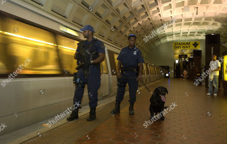 The Washington DC Metro systems, a possible target of terrorist attack has increased security by way of Metro Transit Police armed with automatic weapons and bomb dogs patroling the system and platforms. Here Metro Transit Police Sgt Greg Hanna (with MP5 weapon) and Canine Officer Anthony Montgomery and his dog, Saber patrol a Metro subway platform.