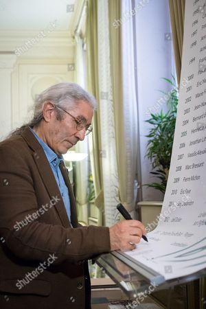 Boualem Sansal signs a register having been awarded the Novel Grand Prix