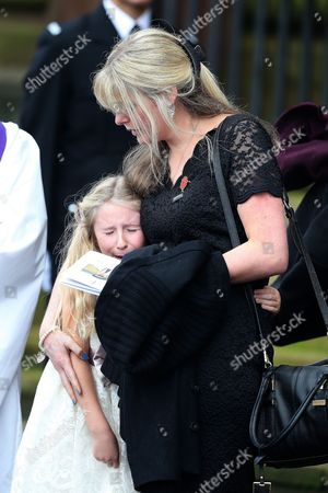 Stock Image of Jen Phillips comforts daughter Abigail on the steps of Liverpool Anglican Cathedral after the service of  PC Dave Phillips in Liverpool, Merseyside