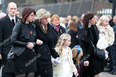 The family of PC Dave Phillips Pictured Lt:R: Kate Phillips, Jen Phillips, Abigail Phillips, Hannah Whieldon, and Sophie Phillips follow the cortege as it makes its way down the Strand, Liverpool past Police HQ, Liverpool, Merseyside.