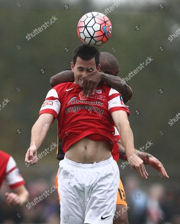 Josh Dutton-Black of Didcot heads the ball under pressure from Clinton Morrison of Exeter   during the FA Cup First  Round  match between Didcot Town and Exeter City    played at Loop Meadow Stadium , Didcot on 8 November 2015