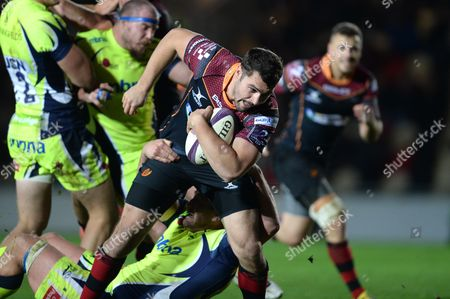 Charlie Davies of Newport Gwent Dragons is tackled by Jonathan Mills of Sale Sharks.