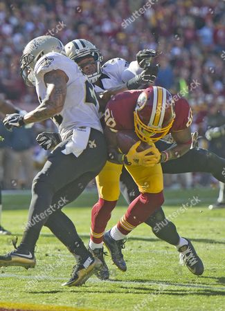 Washington Redskins wide receiver Jamison Crowder (80) scores his team's second first quarter touchdown against the New Orleans Saints at FedEx Field in Landover, Maryland. New Orleans Saints defensive back Kyle Wilson (24) and free safety Jairus Byrd (31) defend on the play.