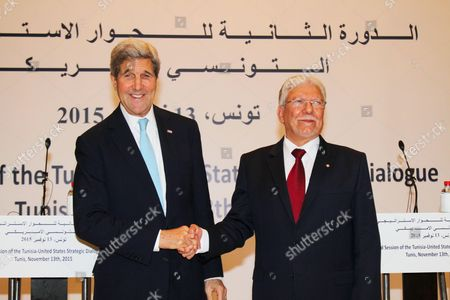 Tunisian Foreign Minister Minister Taieb Baccouche (R) greets US Secretary of State John Kerry