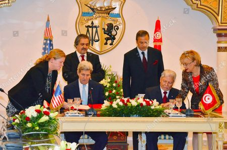 US Secretary of State John Kerry (2-L) signs documents with his Tunisian counterpart Taieb Baccouche