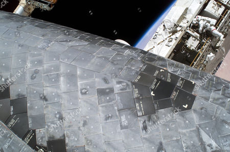 Stock Image of In Earth Orbit. A close up view of a portion of the thermal protection tiles on Space Shuttle Discovery's underside is featured in this image photographed by astronaut Stephen K. Robinson (out of frame), STS-114 mission specialist, during the mission's third session of extravehicular activities (EVA). While perched on a Space Station truss, astronaut Soichi Noguchi (background), mission specialist representing Japan Aerospace Exploration Agency (JAXA), acts as observer and communication relay station between fellow spacewalker Robinson and astronaut Andrew S. W. Thomas aboard Discovery.