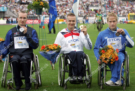 The medalists of 100 m wheelchair, winner David Weir of Great Britain (C), second placed Kenny van Weeghel of Netherlands (L) and Finland's Leo Pekka Tahti who placed third (R)