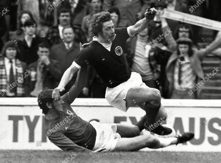 Football - 1975 British Home Championship - Wales 2 Scotland 2 Scotland's Arthur Duncan rides a tackle from Rod Thomas at Ninian Park, Cardiff.