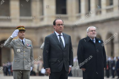 French President Francois Hollande along with Secretary of State for Veterans and Remembrance Jean-Marc Todeschini attends the Autumn military parade in the courtyard of the Hotel des Invalides