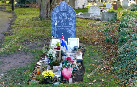 Bee Gee Robin Gibb's grave with tributes from fans with his brother Andy's memorial behind it