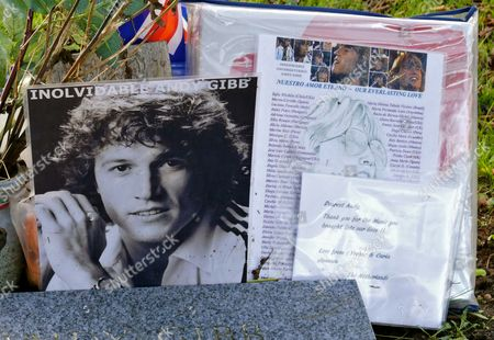 Stock Image of The grave of Andy Gibb with tributes from fans behind his brother Robin Gibb's grave