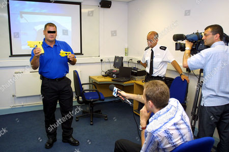 A weapons training officer from the Essex Police Tactical Firearms Group demonstrates the X26 Taser to the county's media prior to the weapon's imminent launch. The X26 Taser will be fully available for deployment in all Essex firearms operations from the 31st of this month (August 2005). Also watching the demo is Chief Inspector Kevin Bailey, who is in charge of firearms operations for Essex Police (second from left).