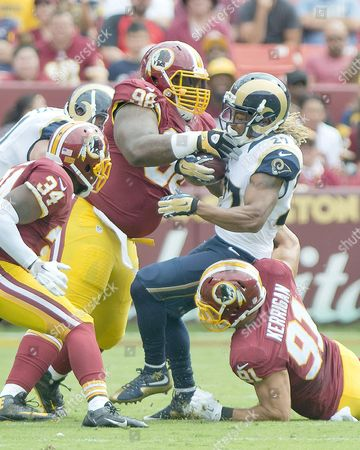 St. Louis Rams running back Tre Mason (27) is tackled by Washington Redskins defensive tackle Terrance Knighton (98) and outside linebacker Ryan Kerrigan (91) in first quarter action  Washington Redskins free safety Trenton Robinson (34) is at left.