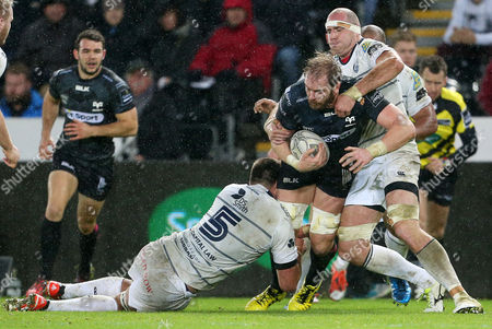 Alun Wyn Jones of Ospreys is tackled by James Down and Lou Reed of Cardiff Blues.