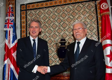 Britain's Foreign Secretary Philip Hammond (L) shakes hands with his Tunisian counterpart Taieb Baccouche during their meeting