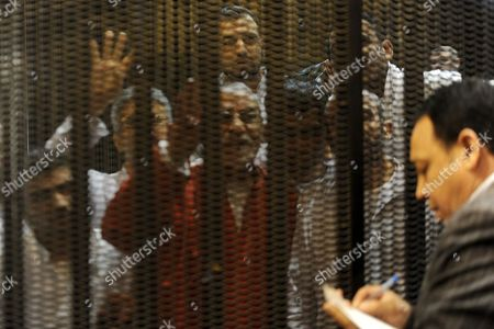 Egyptian Muslim Brotherhood leader Mohammed Badie sits behind the defendant's cage as he attends his trial