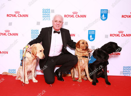 Dave Spikey on the red carpet accompanied by guide dog puppies, at the London Hilton on Park Lane. The Guide Dogs Annual Awards celebrates the life-changing work of the charity.