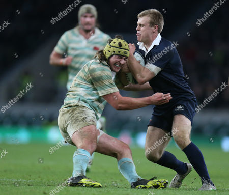 Oxford's Henry Hughes  gets tackled by Cambridge's Max Montgomery
