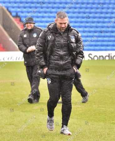 Oldham Athletic Manager, David Dunn trudges off the field as the game is cancelled  during the Sky Bet League 1 match between Oldham Athletic and Millwall at Boundary Park, Oldham