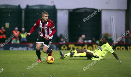 Brentford defender Jake Bidwell leaving Hudderfield Town striker Ishmael Miller on the floor during the Sky Bet Championship match between Brentford and Huddersfield Town at Griffin Park, London