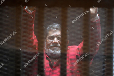 Ousted Egyptian president Mohamed Morsi gestures as he sits behind bars during his trail in a court in Cairo