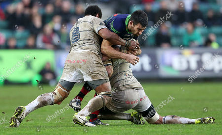 Nick Crosswell of Newport Gwent Dragons is tackled by Manoa Vosawai and Lou Reed of Cardiff Blues.