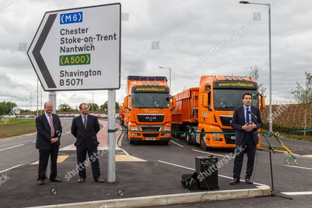 (L to R) Councillor David Brown of Cheshire Highways and Ian Pritchard from developers Goodman look on as Edward Timpson MP speaks; while lorries from Mornflake are queued to be the first vehicles on the new Basford West Spine Road. It is to be named Jack Mills Way after the late local train driver who was attacked during the Great Train Robbery of 1963.