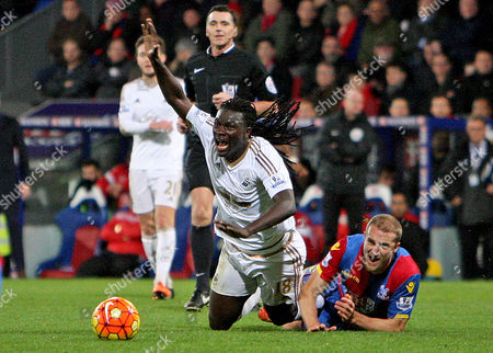 Bafe Gomis of Swansea is fouled by Brede Hangeland of Palace.