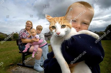 Marmalade the cat, who spent almost 24 hours clinging precariously to a power cable before being rescued by the RSPCA. She is pictured at home, safe and well with family, Sonia Baker and children Kieran 3yrs (holding cat), Chelsea 6yrs and baby Shannon 17months