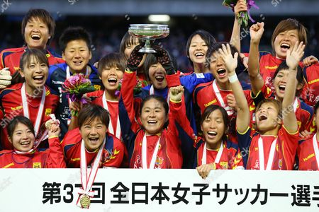 Homare Sawa of INAC Kobe Leonessa holds up the trophy as she celebrates with her teammates