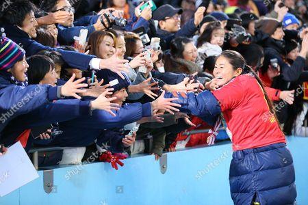 Homare Sawa of INAC Kobe Leonessa high-fives fans
