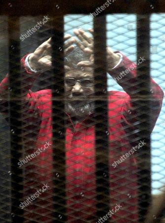 Ousted Egyptian president Mohamed Morsi gestures as he sits behind bars during his trail as part of the so-called 'Qatar espionage' case
