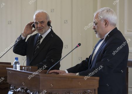 Iraqi Foreign Minister Ibrahim al-Jaafari (L) smiles as he speak with media during a joint news conference with his Iranian counterpart Mohammad Javad Zarif in a Foreign Ministry building