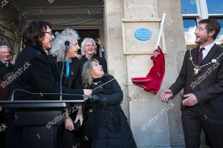 Black Sabbath guitarist Tony Iommi, Queen guitarist Brian May and Suzi Quattro unveil a plaque as Cirencester Mayor Mark Harris (R) looks on