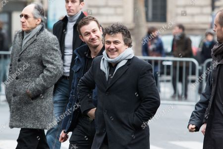 France, Paris. Patrick Pelloux leaves after the anniversary ceremony on Place de le Republique surrounded by his 24/7 police protection alongside Charlie Hebdo Editor in Chief Gerard Biard (far left)
