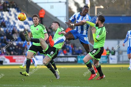 Marvin Sordell of Colchester United tangles with Chris Basham (L) and John Brayford of Sheffield United