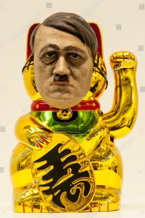 A work by surrealist Nancy Fouts, which juxtaposes a mask of Adolf Hitler onto a Japanese Neko lucky charm cat