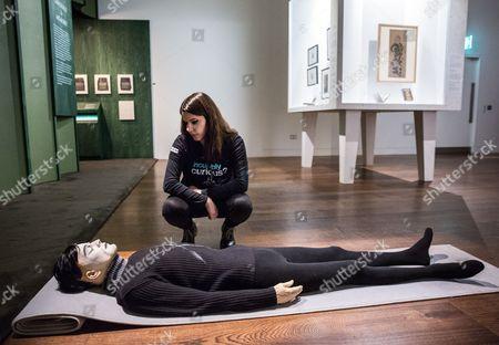 A woman looking at 'Somnambulist' (2006) by Goshka Macuga