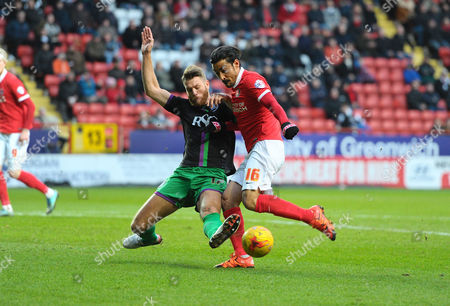Reza Ghoochannejhad of Charlton Athletic gets a shot in as Nathan Baker of Bristol City defends