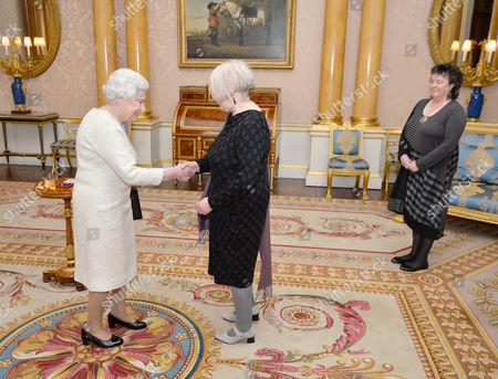 Queen Elizabeth II shakes hands with Liz Lochhead before presenting her with the Queen's Gold Medal for Poetry, accompanied by Poet Laureate Professor Dame Carol Ann Duffy during a private audience, at Buckingham Palace in Westminster central London.