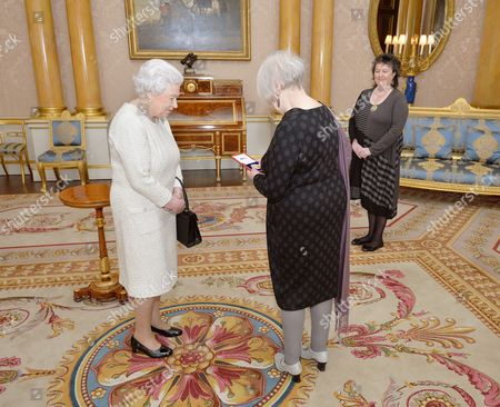 Queen Elizabeth II with Liz Lochhead after she presentd her with the Queen's Gold Medal for Poetry, accompanied by Poet Laureate Professor Dame Carol Ann Duffy during a private audience, at Buckingham Palace in Westminster central London.