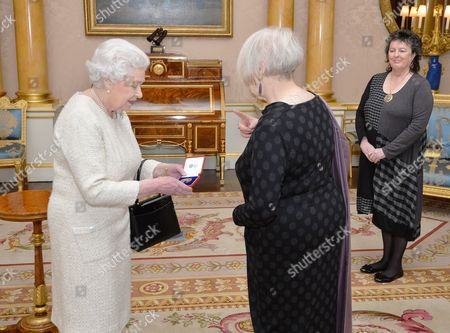 Queen Elizabeth II with Liz Lochhead as she presents her with the Queen's Gold Medal for Poetry, accompanied by Poet Laureate Professor Dame Carol Ann Duffy during a private audience, at Buckingham Palace in Westminster central London.