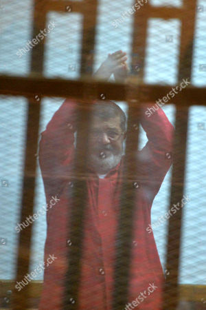Ousted Egyptian president Mohamed Morsi sits behind bars during his trial as part of the so-called 'Qatar espionage' case