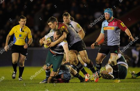 Sam Harrison of Leicester Tigers iswrapped up by Nick Easter and James Horwill of Harlequins during the Aviva Premiership Rugby match between Harlequins and Leicester Tigers played at the Twickenham Stoop, Twickenham on February 19th, 2016