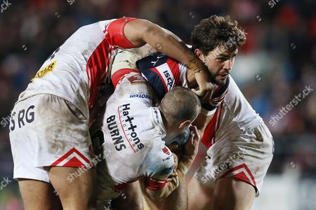 Aidan Guerra is tackled by Lama Tasi, Travis Burns and Luke Thompson during the Dacia Rugby League World Club Series match played between St Helens v Sydney Roosters at Langtree Park, St Helens on February 19th 2016