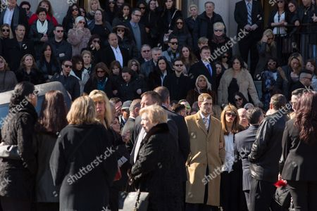 Stock Picture of Anthony A.J. D'Onofrio (Beige trench coat) and Gabriela D'Onofrio leaving the funeral service for his mother Angela Riola outside the Basilica of Regina Pacis on 65th Street in Sunset Park, Brooklyn