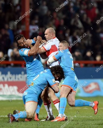 Dane Tilse of Hull KR tackled by St Helens' Travis Burns and St Helens' Atelea Vea during the First Utility Super League match between Hull KR and St Helens at the KC Lightstream Stadium, Hull on the 26th of February 2016.