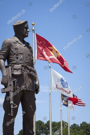The statue of North Carolina native General Hugh Shelton, Ret., that was commissioned and donated by H. Ross Perot stands among an array of military and state flags near the entrance of the Airborne and Special Operations Museum in the North Carolina Veterans Park, Fayetteville, NC.
