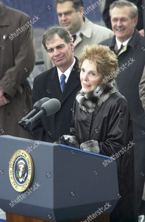 Nancy Reagan speaks at the christening of the newest nuclear aircraft carrier the USS Ronld Reagan, CVN-76. William P. Fricks, president and CEO of Newport News shipbuilding stands at her side. Above right, stand Secretary of Defense Donald Rumsfeld.